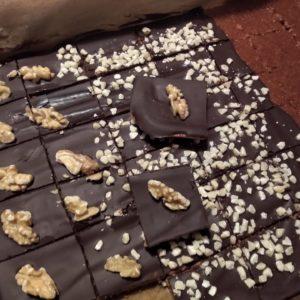 Das Bild zeitgt einen selbstgebackenen Honigkuchen mit Schokoladenüberzug. Es ist ein Blechkuchen der mit Walnüssen und gehackten Mandeln verziert ist.