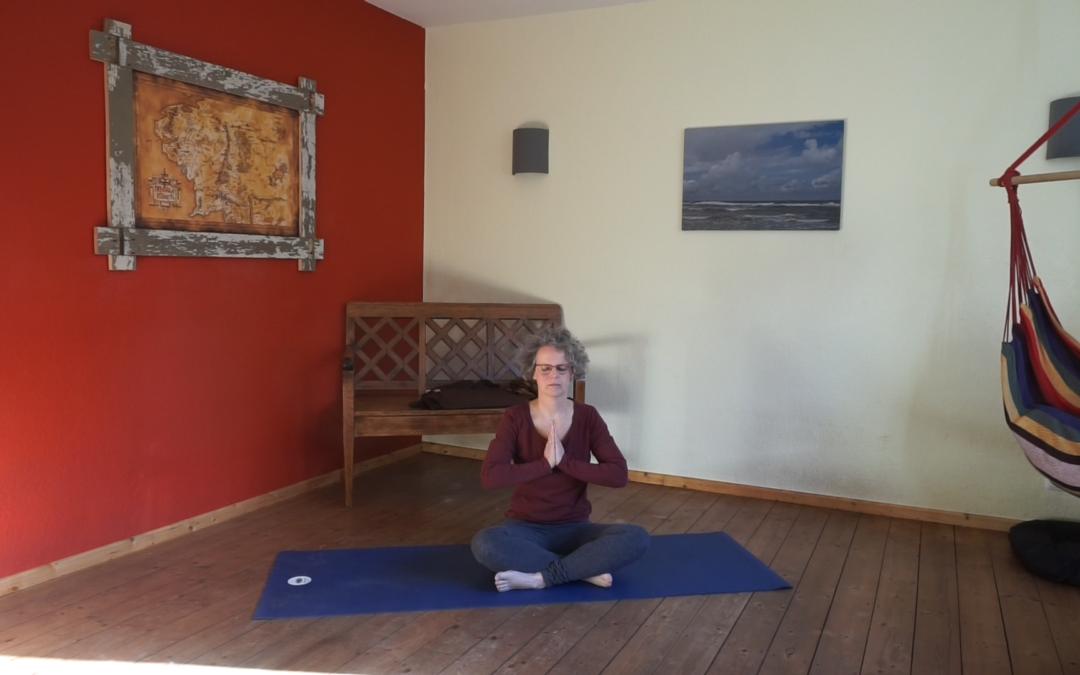 Das Bild zeigt Susanne Koch auf der Yogamatte sitzend. Die Hände sind zum Yogagruß gefaltet.