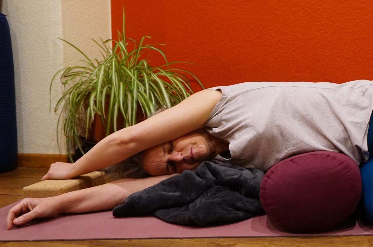 Susanne im der Yin Yogaposition liegende Banane. Sie liegt auf der rechten Seite, ein Yogabolster unter der Tallie. Die Arme sind über dem Kopf ausgestreckt.  Das Foto zeigt nur den Oberkörper. Zur Unterstützung liegt eine Decke unter der Schulter, der linke Arm ist auf einen Yogablock gestützt.