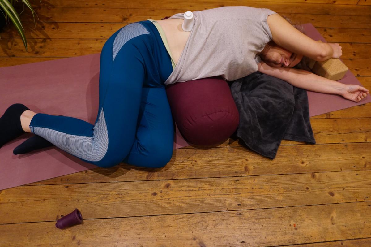 Susanne in der Yin Yogaposition liegende Banane von oben fotografiert. Sie liegt auf der rechten Seite, ein Yogabolster unter der Tallie. Die Arme sind über dem Kopf ausgestreckt. Die Beine sind angewinkelt.. Zur Unterstützung liegt eine Decke unter der Schulter, der linke Arm ist auf einen Yogablock gestützt.
