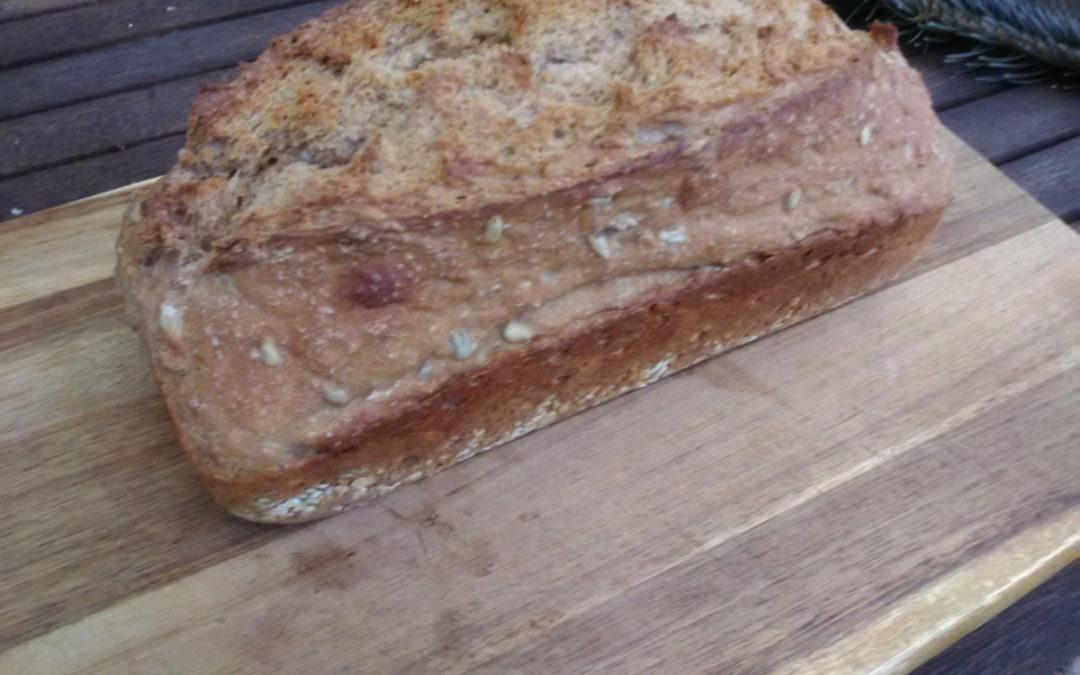 Das Bild zeigt ein Dinkelvollkornbrot in Kastenform gebacken. Es liegt auf einem Holzbrett