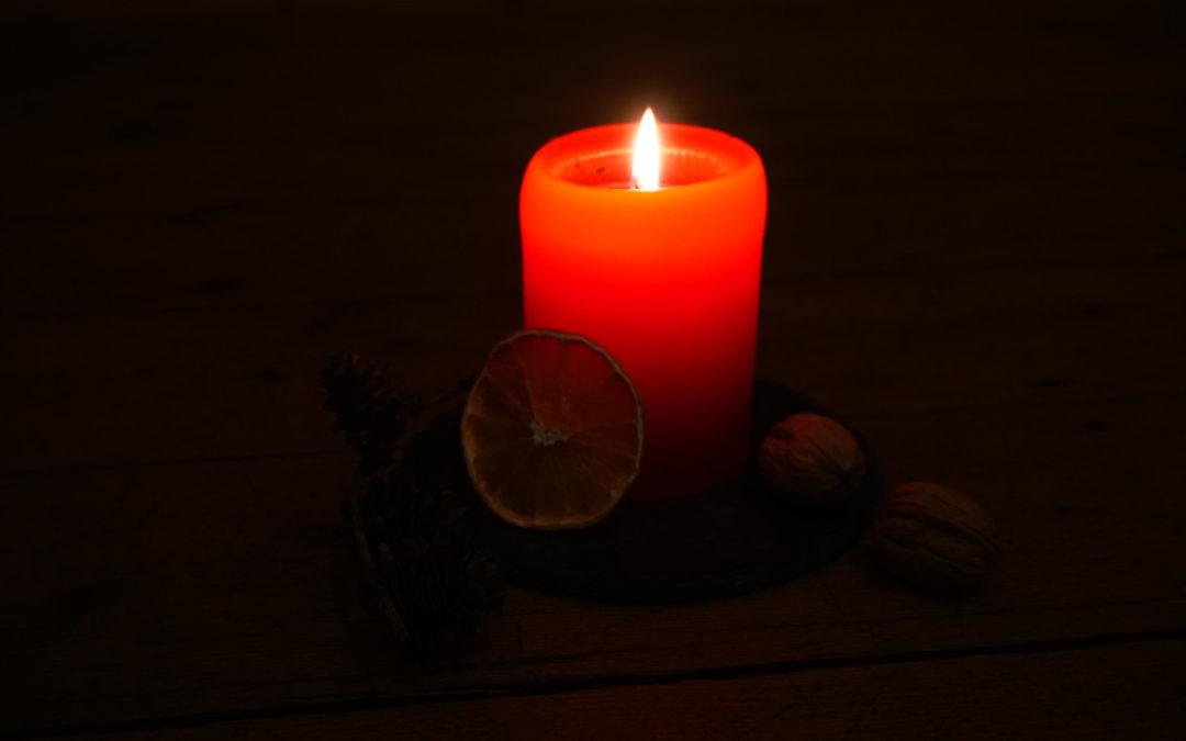 Eine brennende rote Kerze. Der HIntergrund ist dunkel, neben der Kerze liegen eine Orangenscheibe und einige Walnüsse.