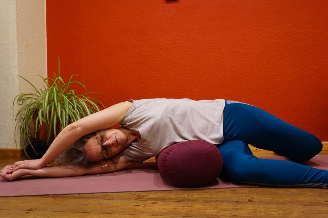 Susanne im der Yin Yogaposition liegende Banane. Sie liegt auf der rechten Seite, ein Yogabolster unter der Tallie. Die Arme sind über dem Kopf ausgestreckt, die Beine angewinkelt