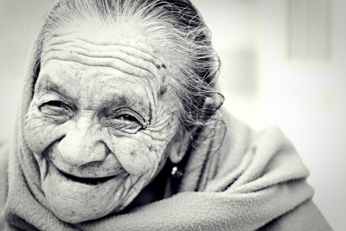 Das Bild zeigt eine lächelnde alte Frau. Lächeln oder auch Gesichtsyoga aus.