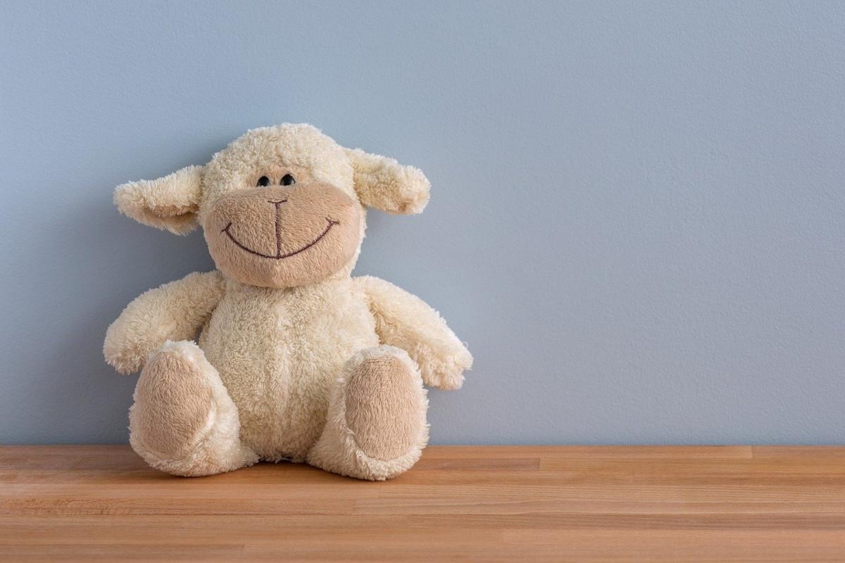 Das Bild zeigt ein lächelndes Stoffschaf. Gesichtsyoga lässt Stofftiere lächeln.