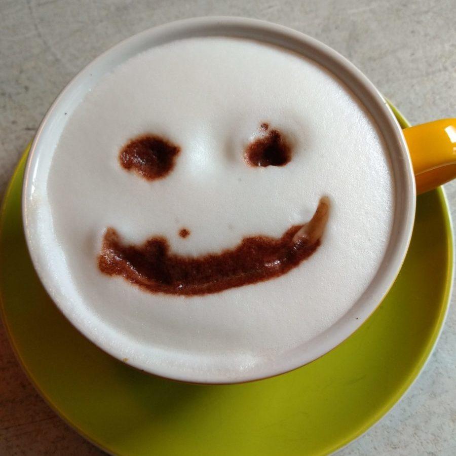 Eine Tasse mit aufgeschäumter Sojamilch und einem mit Kakao gezeichneten lächelndem Gesicht.
