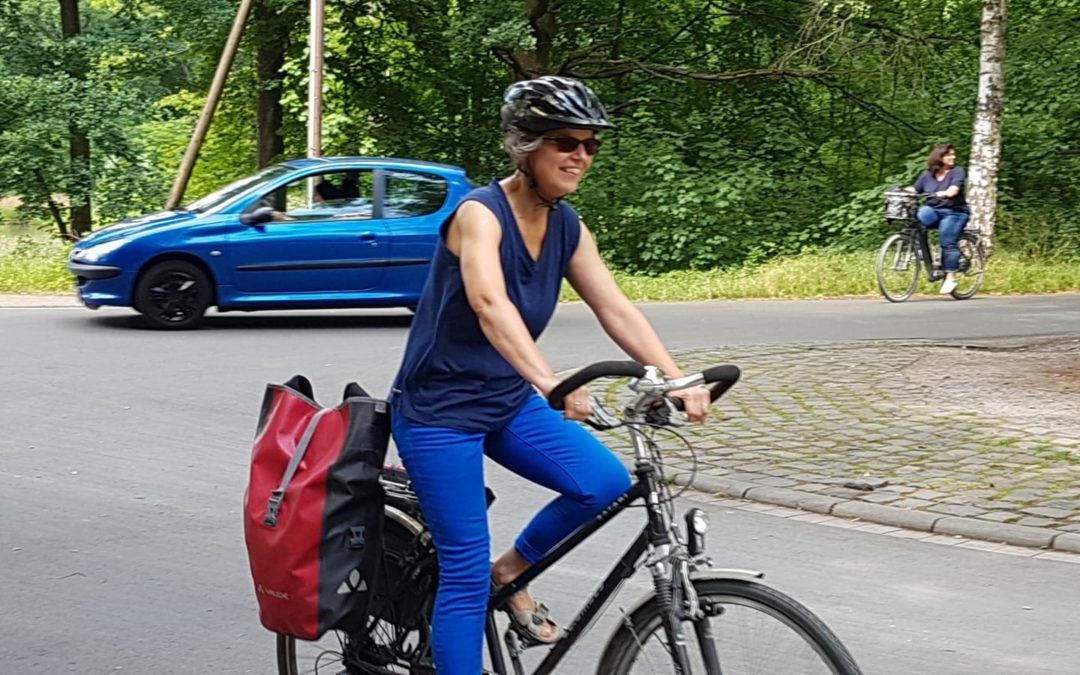 Susanne auf ihrem Fahrrad mit Gepäcktaschen. Ein gutes Beispiel für Nachhaltigkeit- Im Hintergrund ein blaues Auto