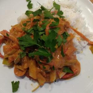 Das Foto zeigt die Gemüsemandelpfanne mit Reis auf einem Teller angerichtet. Sie ist verziert mit gezupfter Petersilie.