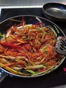Das Foto zeigt auf Streifen genschnittene Paprika, Möhren und Lauch in einer Pfanne. Sie sind vermischt mit Mandelmus.