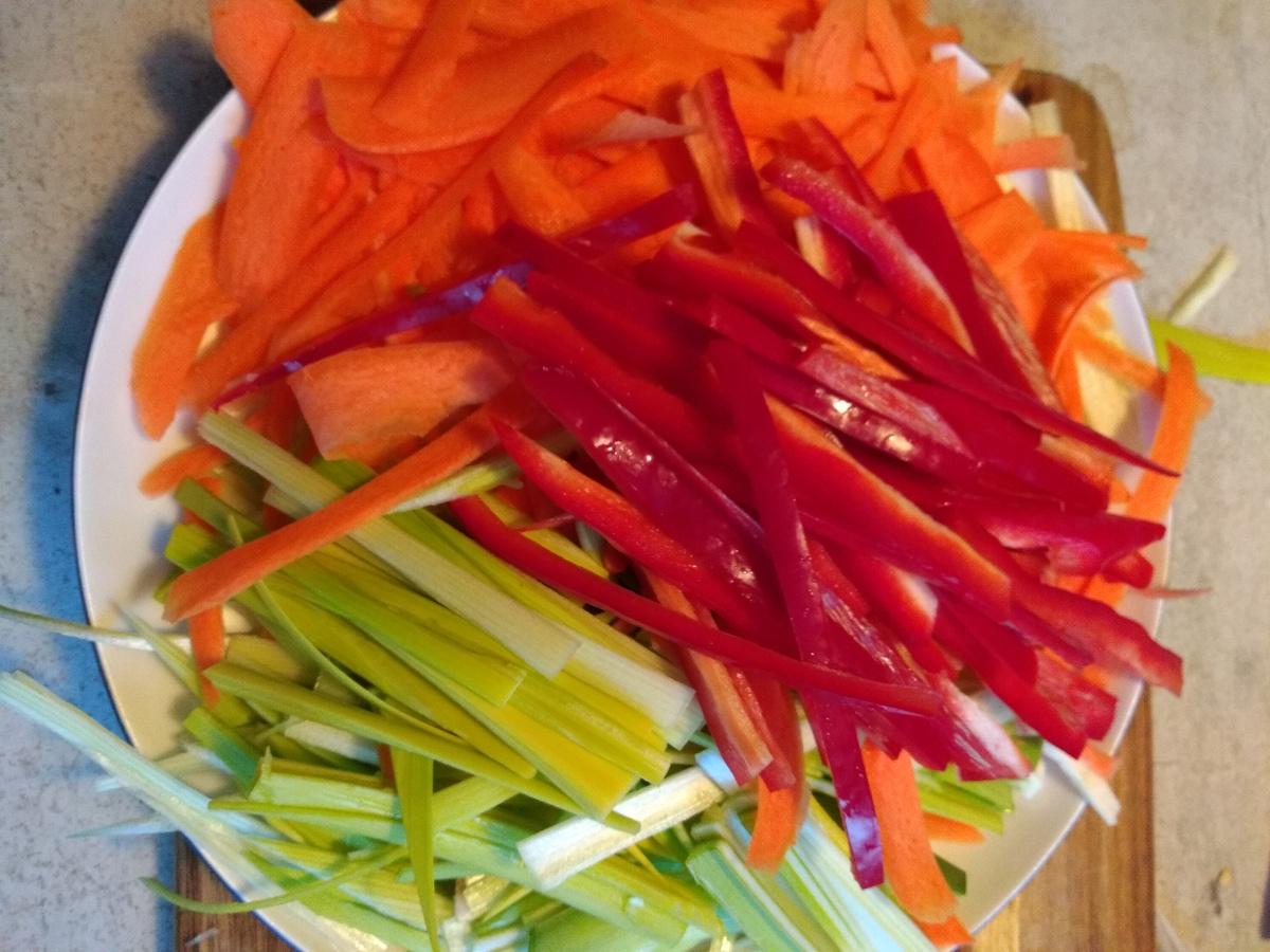 Das Foto zeigt in Streifen gescnittendes Gemüse. Möhren, Paprika und Lauch.