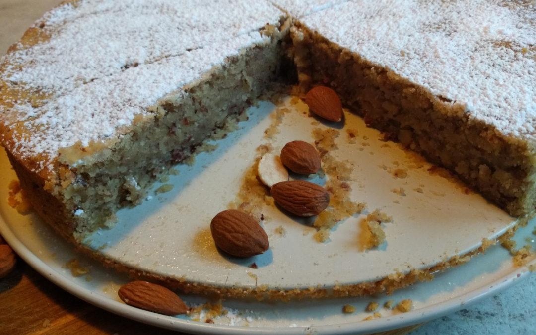 Das Foto zeigt einen spanischen Mandelkuchen in einer Ringform gebacken. Er ist angeschnitten und liegt auf einem Holztablett. Er ist mit Puderzucker bestrut. Daneben liegen einige Mandeln.