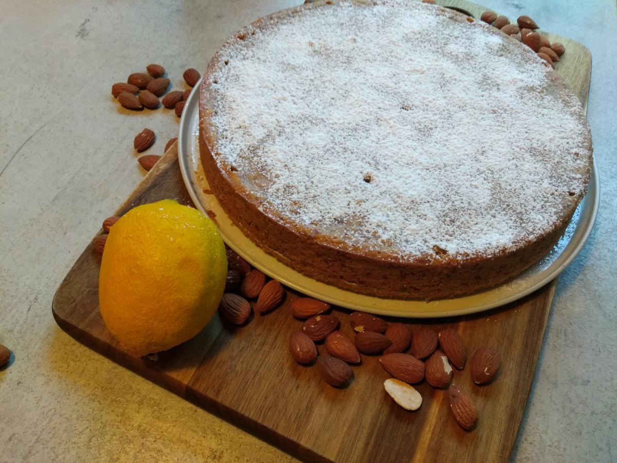 Das Foto zeigt einen spanischen Mandelkuchen in einer Ringform gebacken auf einem Holztablett. Er ist mit Puderzucker bestrut. Daneben liegt eine Zitrone und einige Mandeln.