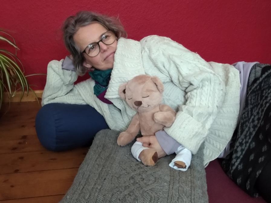Susanne liegend mit einem Yogabär im Arm. Das Bild drückt den ausgleich der Energien Prana oder Chi im Yoga aus. Yin und Yang.