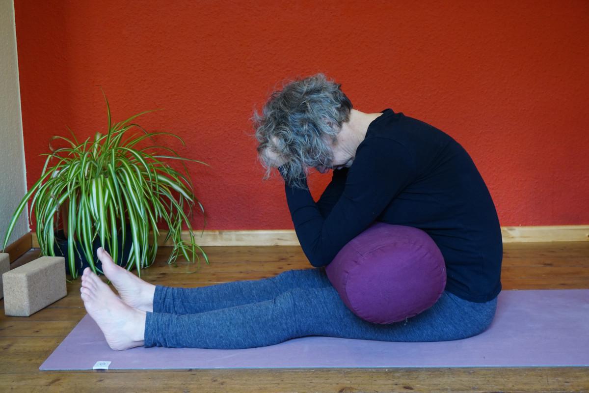 Susanne in der Yin Yoga Position Raupe mit einem Bolster als Hilfsmittel vor dem Bauch.