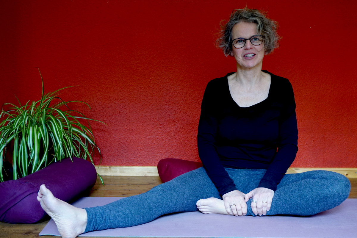 """Susanne in der Yinposition """"halber Schmetterling"""" auf dem Boden sitzend ist ein Bein angewinckelt, das andere ausgestreckt, der Oberkörper aufgerichtet."""