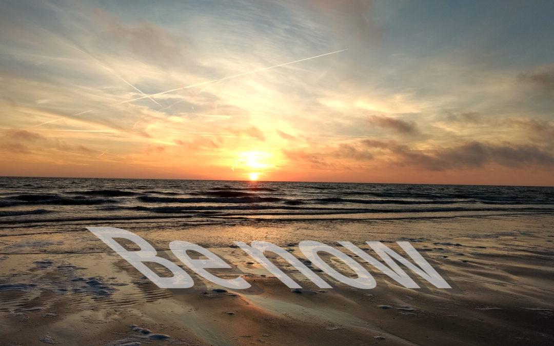 """Das Foto zeigt einen Sonnenuntergang am Strand. Auf dem Strand liegend steht in weißer Farbe """"Be now"""" Im Augenblick leben."""