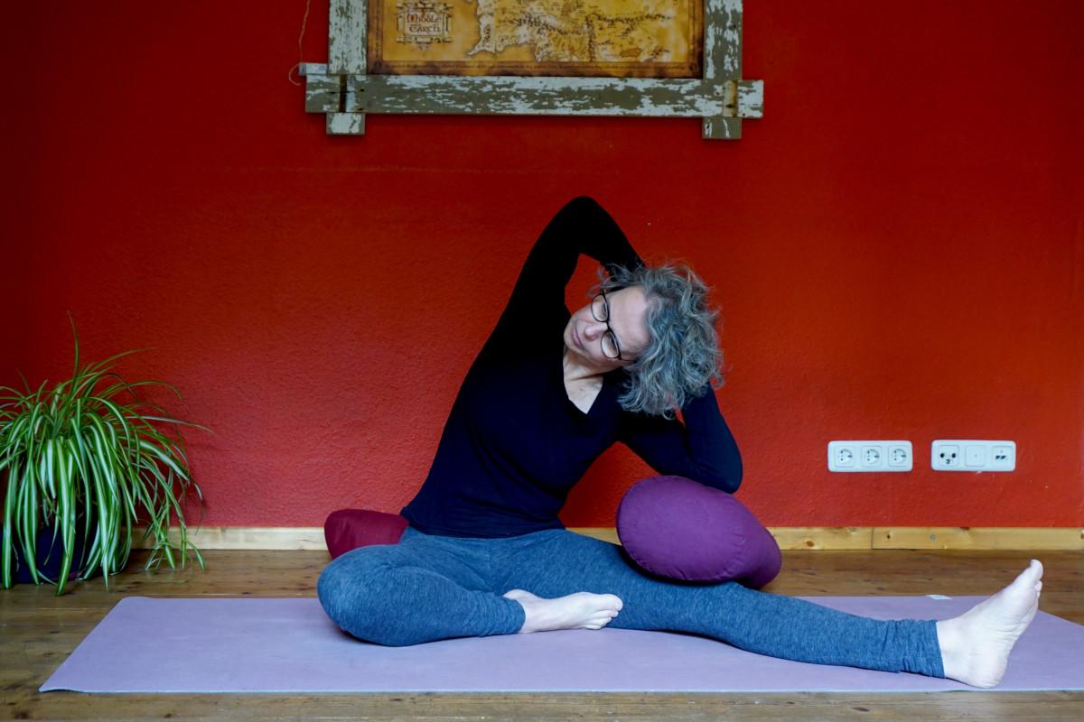 """Susanne in der Yinpsosition """"halber Schmetterling mit Seitbeuge"""" Ein Bein ist auf dem Boden sitzend angewinckelt, das ander ausgestreckt. Der Oberkörper wird zum gestreckten Bein hin gebeugt."""