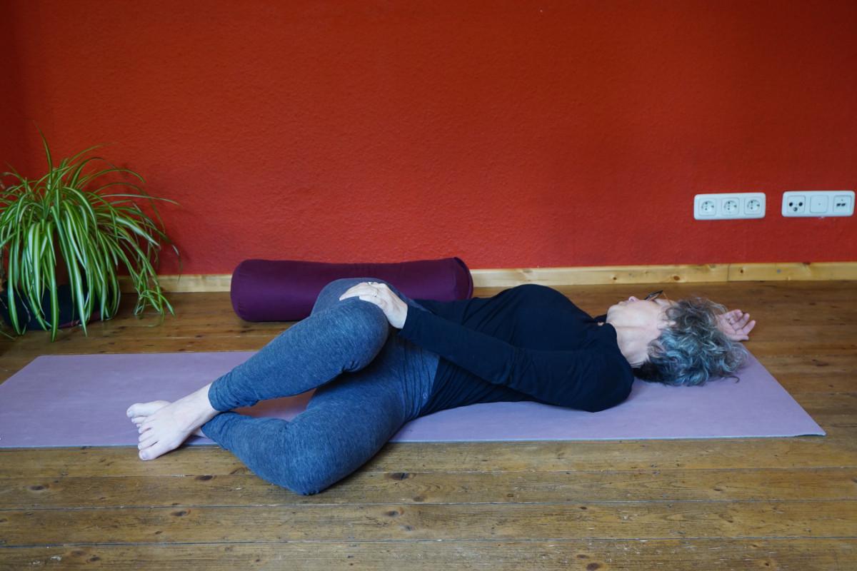 Das Bild zeigt Susanne in der Yin Position Korkenzieher. Dabei werden die Beine gebeugt und nach links abgelegt.