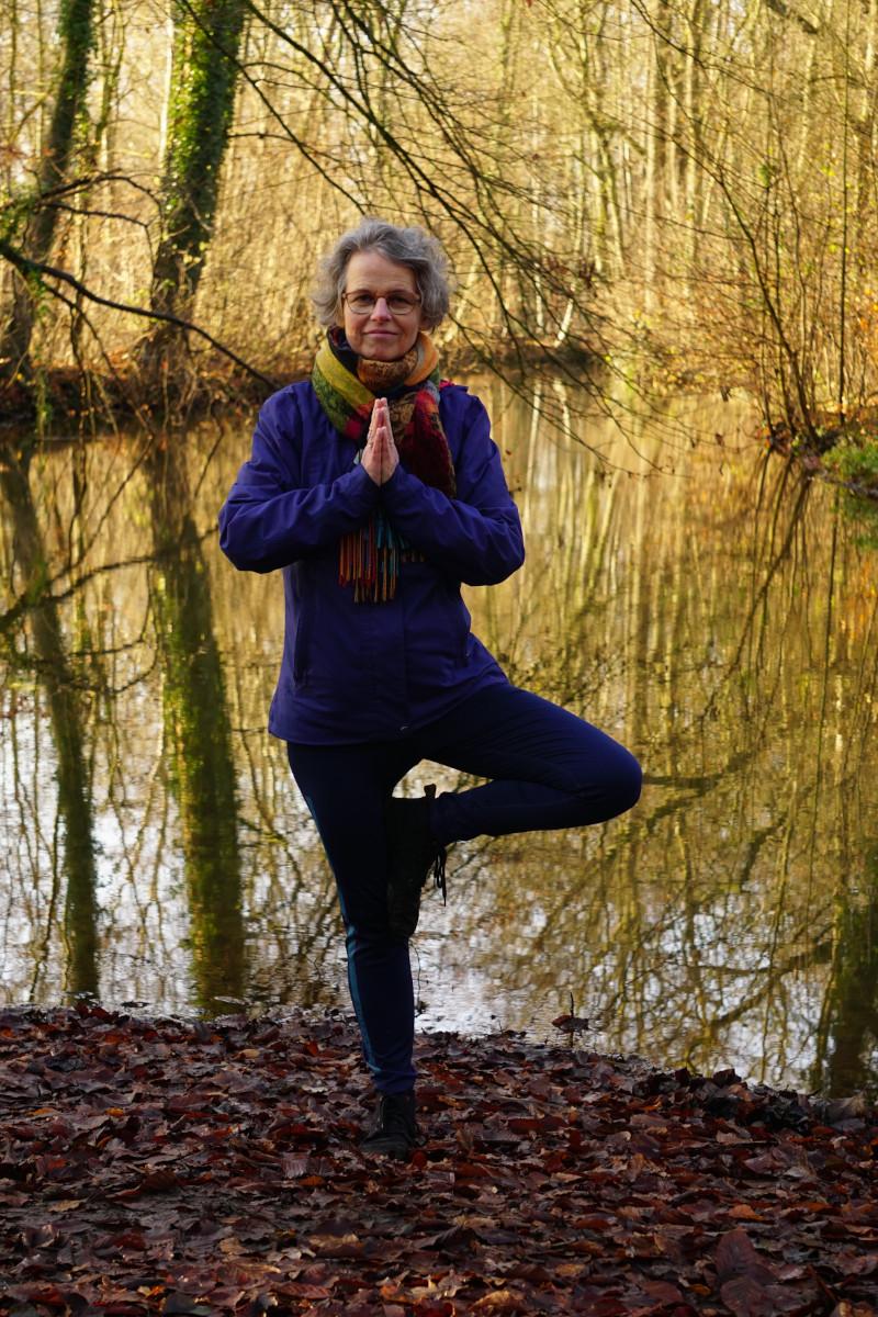 Susanne in der Yogaposition Baum. Im Stehen wird ein Bein angewinkelt und an der Fuß am Oberschenkel angelegt. Die Hände sind gefaltet.
