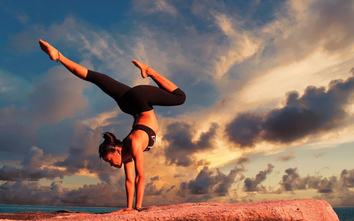 Das Bild zeigt eine Frau im Handstand vor einem Sonnenuntergang