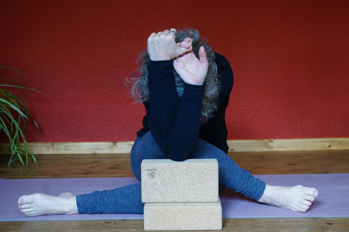 """Susanne in der Yinposition """"Schnürsenkel mit Adlerarmen"""" dabei nutzt sie zwei Blöcke als Hilfsmittel"""