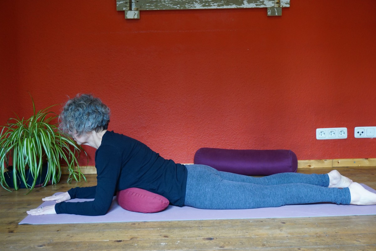 """Das Foto zeigt Susanne in der Yin Position """"Sphinx"""". Dabei liegt der Oberkörper auf einem Bolster die Unterarme sind aufgestützt."""