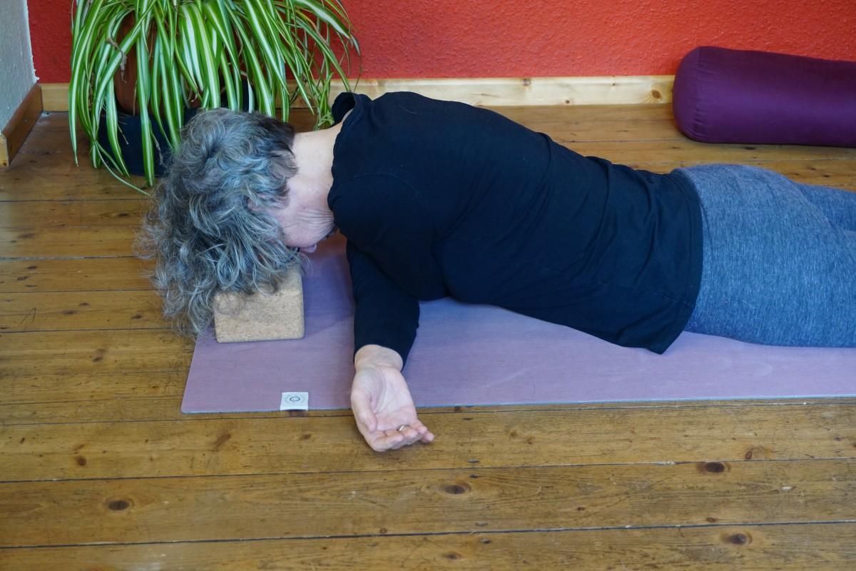 """Susanne in der Yin Position """"umarmende Flügel"""". Dabei liegt sie auf dem Bauch die Arme kreuzen in Schulterhöhe aneinander vorbei."""